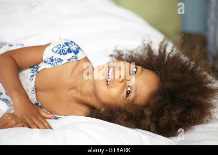 Young mixed race girl, portant l'enfant sur le lit avec des draps blancs en bleu et blanc robe d'été. Banque D'Images