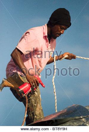 Travailleur sur le toit avec une élingue de sécurité pendant l'utilisation d'un circuit hydraulique (air comprimé) Banque D'Images