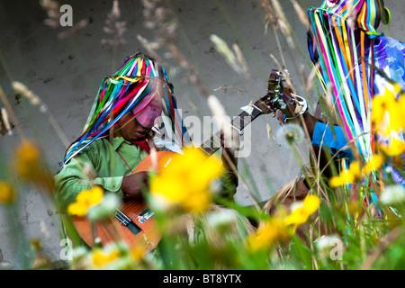 Les hommes, portant des costumes colorés, guitares jouer pendant la fête de l'Inti Raymi dans la province de Pichincha, Banque D'Images