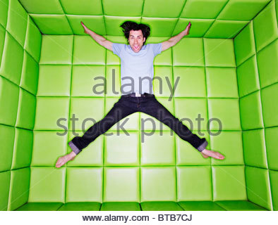 Man jumping in padded room Banque D'Images