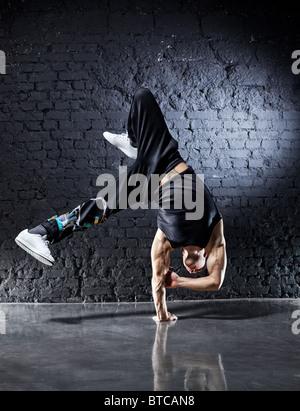 Jeune homme fort break dance. Sur le mur sombre arrière-plan. Banque D'Images