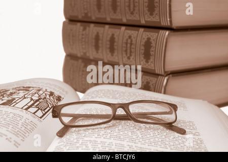 Plus de verres vieux livre ouvert avec de vieux livres flou en arrière-plan, en sépia Banque D'Images