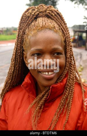Portrait of a smiling Venda femme avec une coiffure tressée.