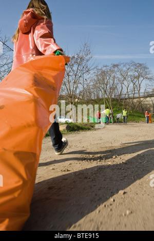 Ramasser les détritus, faisant glisser le sac à déchets Banque D'Images