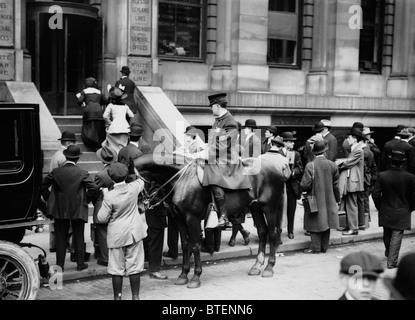 Un policier à l'extérieur des patrouilles la White Star Line des bureaux à New York, comme les foules se rassemblent à la suite de la catastrophe du Titanic en 1912.