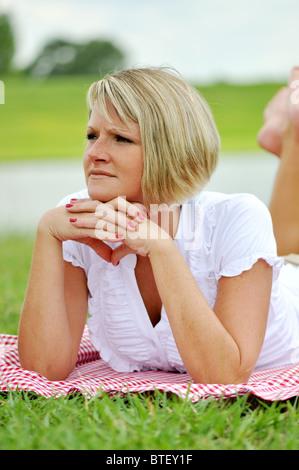 Young blonde woman lying on blanket Vichy en plein air au bord du lac.