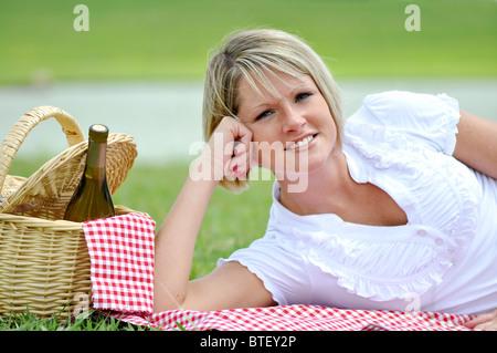 Jeune femme blonde au bord du lac de pique-nique avec vin et panier. Allongé sur une couverture vichy.