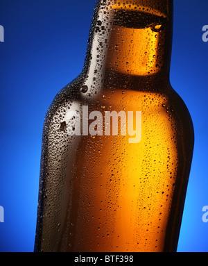 Bouteille de bière avec des gouttes sur un fond bleu. Fermer une partie de la bouteille. Banque D'Images