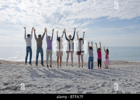 Groupe de personnes à la plage, bras levés Banque D'Images