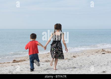 Les enfants courent ensemble à la plage, se tenant la main