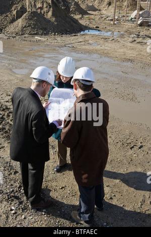 Réunion avec l'architecte ingénieurs at construction site discussing blueprints