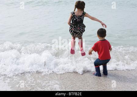 Enfants jouant dans le surf à la plage Banque D'Images