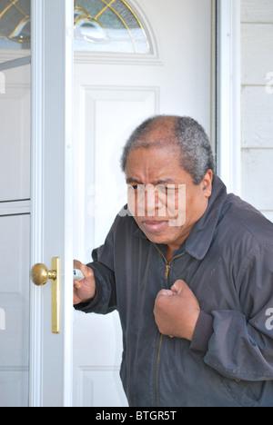 African American man avoir une crise cardiaque tout en laissant sa maison. Banque D'Images