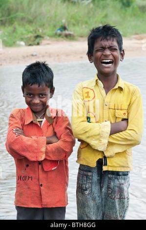 Les jeunes Indiens pauvres garçons tirant une drôle de visages et de rire. L'Inde Banque D'Images