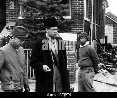 Malcolm X (1925-1965), centre, parle à un journaliste après un incendie Molotov a été lancé dans sa maison. 14 février, Banque D'Images