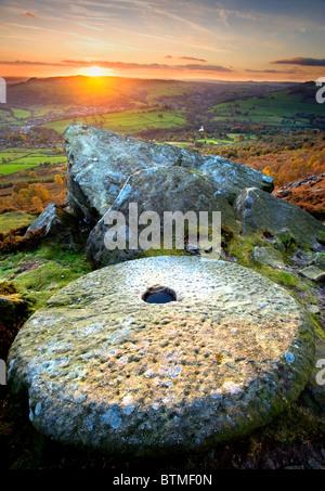 Meule abandonnée au coucher du soleil sur le bord Curbar, parc national de Peak District, Derbyshire, Angleterre, Banque D'Images