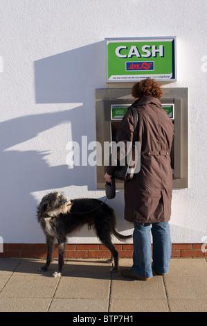 Femme avec chien faire des retraits d'espèces au distributeur automatique de billets