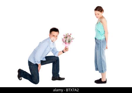 Heureux beau jeune homme remettant un fleurs pour une belle jeune femme isolée sur fond blanc Banque D'Images