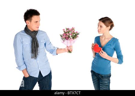 Jeune beau couple dans l'amour. Woman coeur, l'homme qui offre des fleurs, isolé sur fond blanc. Banque D'Images