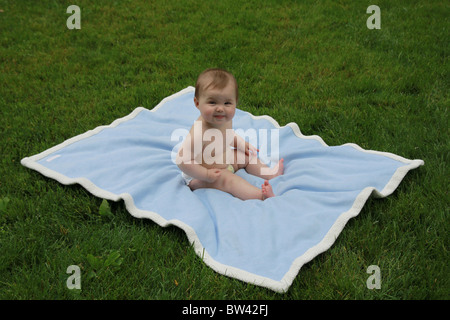 A 6 mois du garçon assis sur une couverture bleue dans les champs Banque D'Images