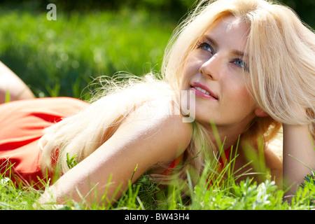 Photo de blonde lying luxe in Green grass in park
