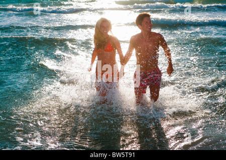 Cple courir en mer tenir la main dans le coucher du soleil Banque D'Images