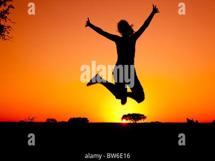 Silhouette d'une jeune femme sautant au coucher du soleil