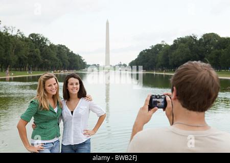 Jeune homme de prendre la photo d'amis à Washington monument Banque D'Images
