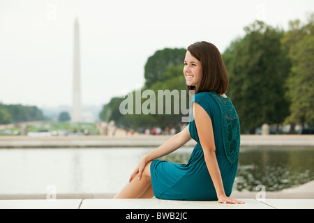 Girl par reflecting pool avec Washington monument à distance