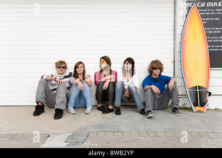 Friends sitting on floor with surfboard Banque D'Images