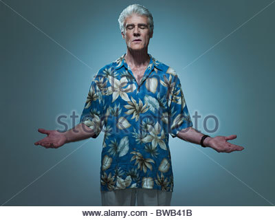 Senior man wearing hawaiian shirt posant comme Jésus, portrait Banque D'Images