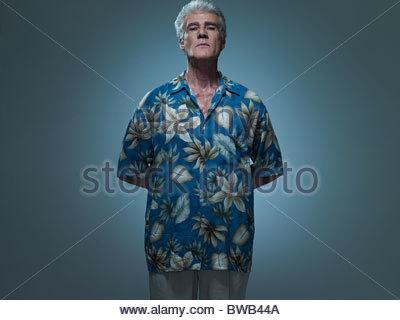 Hauts homme portant chemise hawaïenne avec les mains derrière le dos, portrait Banque D'Images