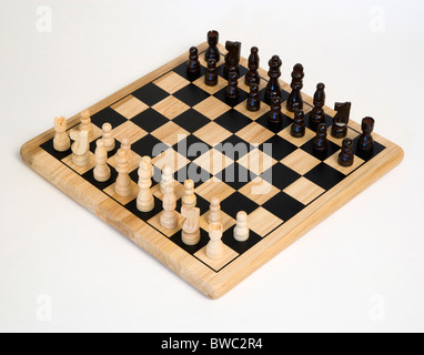 Jouets, jeux, jeux de société, d'échecs avec des pièces prévues pour début de match contre un fond blanc.