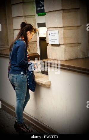 Une jeune femme à l'aide d'un distributeur automatique ATM Lloyds TSB, UK