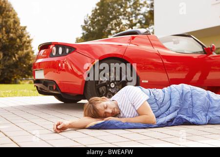 L'homme dort à côté de sa voiture électrique Banque D'Images
