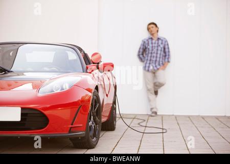 Jeune homme de remplir sa voiture électrique