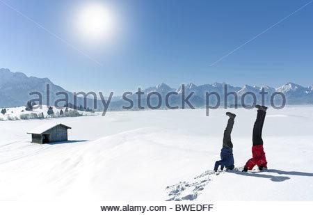 Couple faire headstands dans la neige Banque D'Images