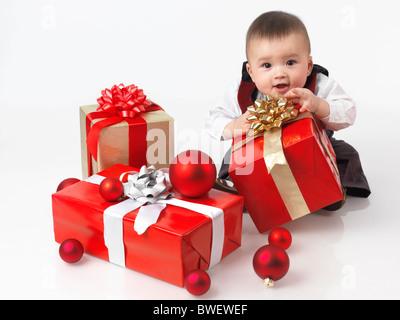 Heureux à l'âge de six mois, bébé garçon l'ouverture des cadeaux de Noël. Isolé sur fond blanc. Banque D'Images