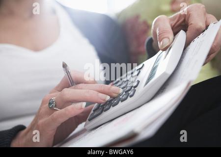 Close-up of woman's hands sur calculatrice Banque D'Images