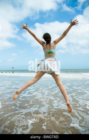 Jeune fille bondit sur bord de l'eau Banque D'Images