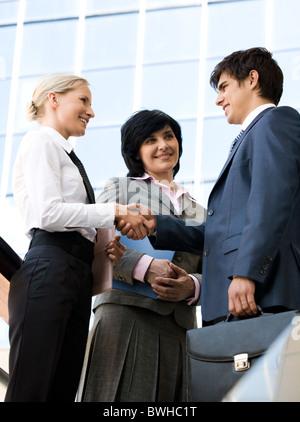 Photo d'entreprise à succès partenaires l'établissement de liaison après la signature de contrat, alors que leur collègue à les regarder