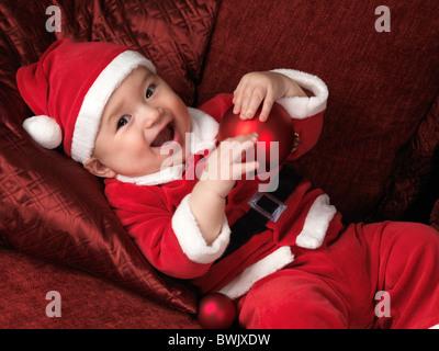 À l'âge de six mois, Happy smiling baby boy in Santa costume Noël allongé sur un canapé avec une boule rouge dans Banque D'Images
