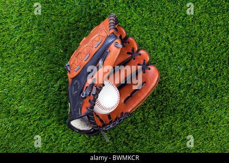 Photo d'un gant de baseball et balle sur l'herbe. Banque D'Images