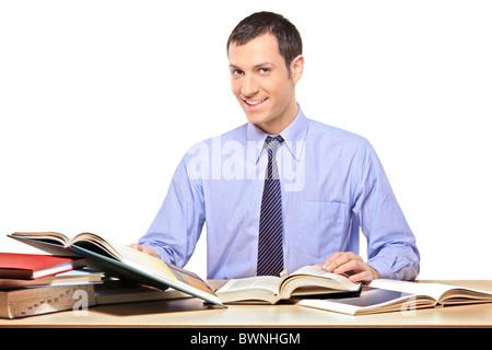 Un homme heureux de lire un livre, avec beaucoup d'autres livres sur le bureau Banque D'Images
