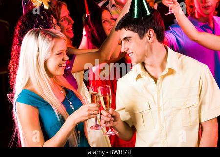 Portrait of happy couple avec des flûtes de champagne avec leurs amis sur le contexte Banque D'Images