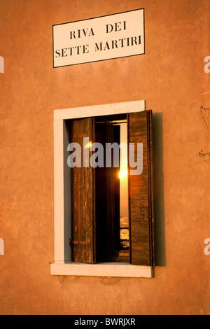 Une fenêtre dans une chambre donnant sur la lagune de Venise sur la Riva dei Sette Martiri. Banque D'Images