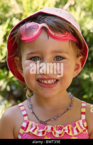 Trois ans girl wearing sun hat maillot et à tout droit à l'appareil photo et de sourire. Banque D'Images