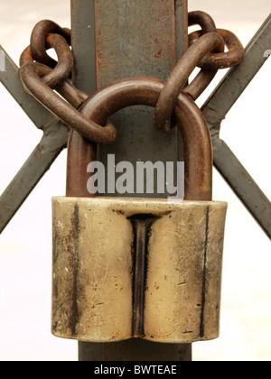Le vieux cadenas et chaîne rouillée sur un treillis métallique. Banque D'Images
