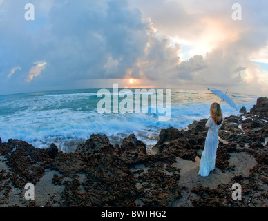 Young woman holding umbrella standing on rocks near ocean Banque D'Images
