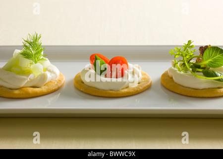 Les craquelins avec du fromage crémeux propagation, garni de tomates, basilic, concombre, aneth, mixte et de radis Banque D'Images